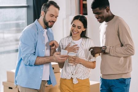 Photo pour Collègues de travail souriants avec café pour aller parler et regardant smartphone tout en déplaçant au nouveau bureau - image libre de droit