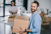 handsome bearded man holding cardboard boxes and smiling at camera while relocating with female colleague in new office