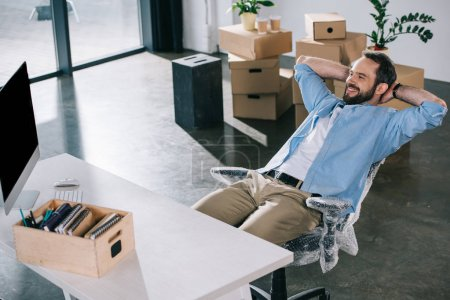 happy businessman sitting with hands behind head and looking away in new office during relocation