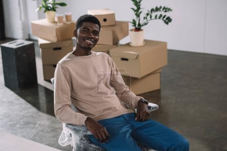 Photo pour Vue de la forte inclinaison du jeune homme d'affaires américain, souriant à la caméra tout en se reposant dans le nouveau bureau au cours de la réinstallation - image libre de droit