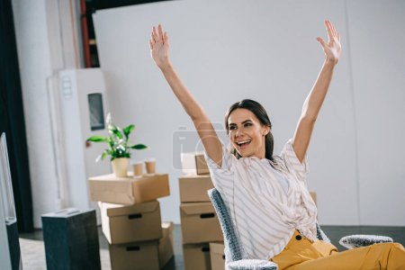excited young businesswoman raising hands and looking away in new office