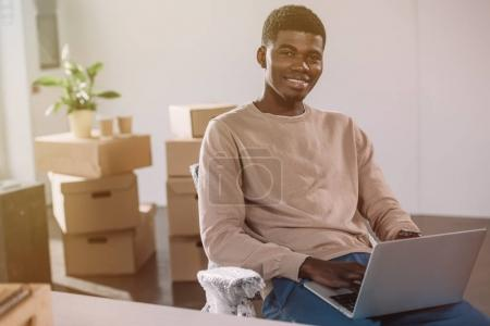 Photo for Handsome african american man using laptop and smiling at camera while sitting in new office during relocation - Royalty Free Image