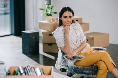 Photo pour Jeune femme d'affaires regardant la caméra tout en étant assis dans un nouveau bureau lors de la relocalisation - image libre de droit