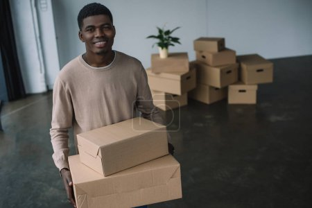 Photo for Happy african american man holding boxes and smiling at camera while relocating in new office - Royalty Free Image