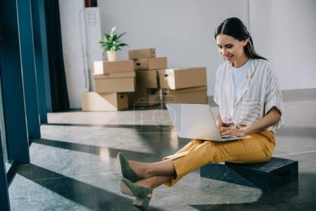 smiling young woman using laptop while sitting in new office during relocation