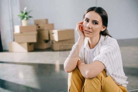 beautiful young woman looking at camera while sitting in new office during relocation