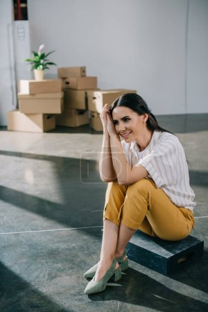 happy young woman looking away while sitting in new office during relocation