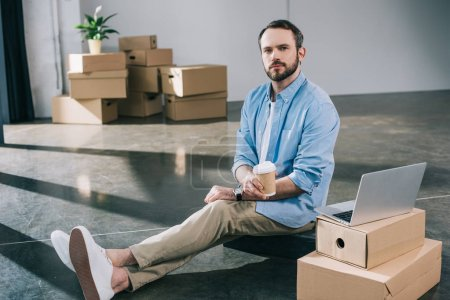 businessman holding coffee to go and looking at camera while sitting on floor in new office