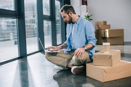 bearded businessman using laptop while sitting on floor in new office