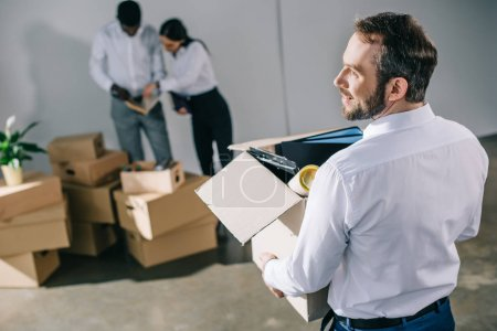 Back view of businessman holding cardboard box with office supplies while colleagues unpacking boxes in new office