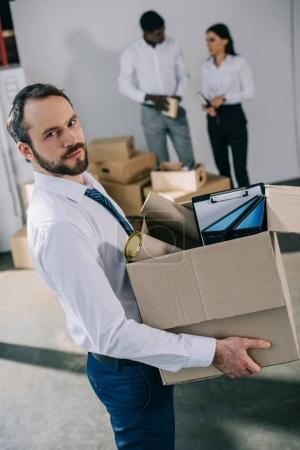 businessman holding cardboard box with office supplies and looking at camera while colleagues standing behind in new office