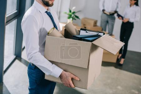 Photo pour Recadrée tir d'homme d'affaires maintenant et boîte en carton en déplaçant avec des collègues de bureau nouveau - image libre de droit