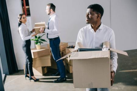Photo for Smiling african american businessman holding cardboard box while relocating with colleagues in new office - Royalty Free Image