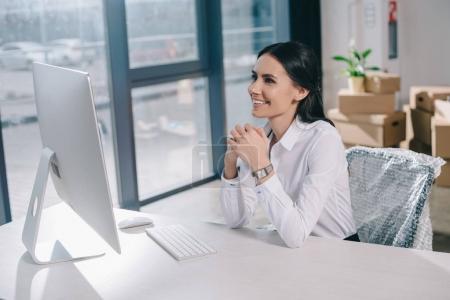 Foto de Feliz empresaria joven con computadora de escritorio mientras está sentado en el lugar de trabajo en nueva oficina - Imagen libre de derechos
