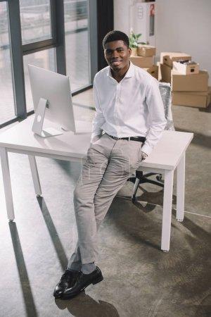 Photo pour Vue sur angle haute heureux homme d'affaires américain souriant à la caméra tout en étant assis sur la table dans le nouveau bureau - image libre de droit