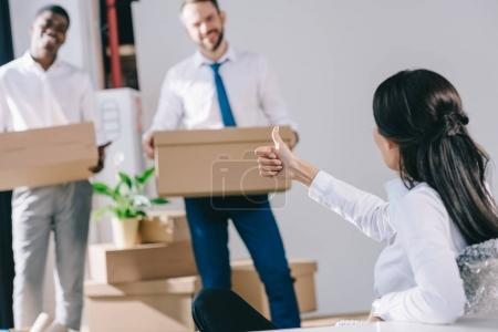 businesswoman showing thumb up to male colleagues holding cardboard boxes in new office