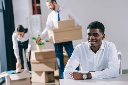 young african american businessman smiling at camera while colleagues unpacking boxes in new office