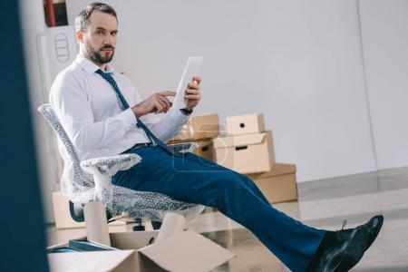 Photo pour Homme barbu à l'aide de tablette numérique et regardant la caméra tout en se reposant dans le nouveau bureau - image libre de droit