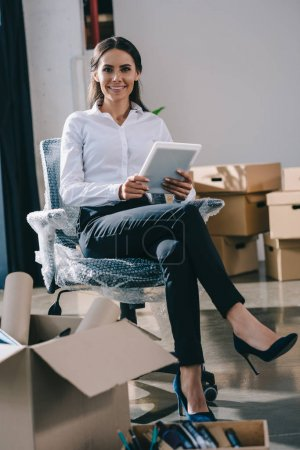 Photo pour Heureux jeune femme d'affaires à l'aide de tablette numérique et souriant à la caméra tout en se reposant dans le nouveau bureau - image libre de droit