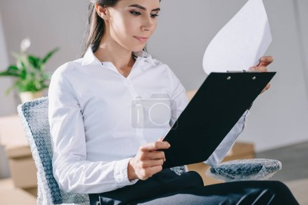 focused young businesswoman holding clipboard in new office