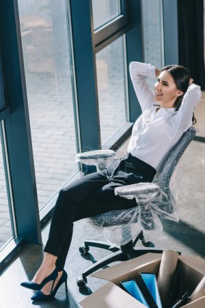 high angle view of happy young businesswoman sitting with hands behind head and looking away in new office