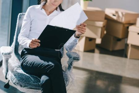 Photo for Cropped shot of young businesswoman holding clipboard while sitting in new office during relocation - Royalty Free Image