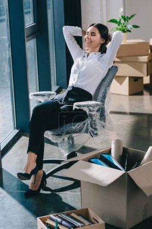 Photo pour Heureux jeune femme d'affaires assis avec les mains derrière la tête dans le nouveau bureau - image libre de droit