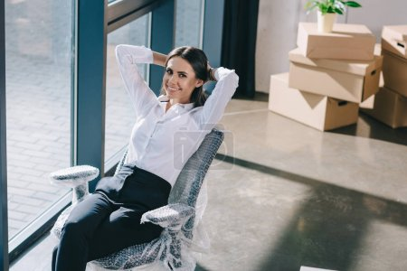 Photo for High angle view of happy young businesswoman sitting with hands behind head and smiling at camera in new office - Royalty Free Image