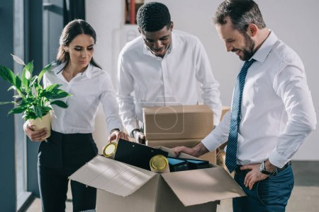 multiethnic business people in formal wear unpacking boxes in new office