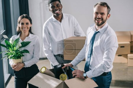 Foto de Alegres compañeros multiétnicos desembalar cajas en nueva oficina - Imagen libre de derechos