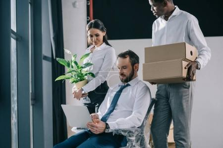 multiethnic business people with laptop, boxes and potted plant moving in new office
