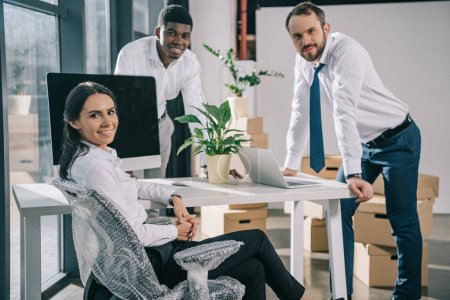 Photo for Happy multiracial coworkers smiling at camera while moving in new office - Royalty Free Image