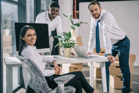 Foto de Compañeros de trabajo multirraciales felizes sonriendo a cámara mientras se mueve en nueva oficina - Imagen libre de derechos