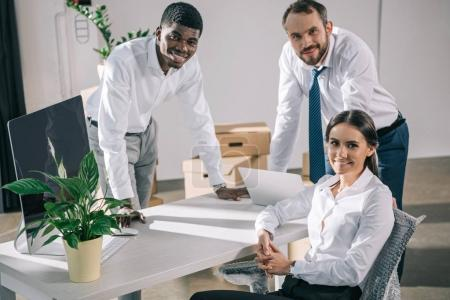 happy multiracial coworkers smiling at camera while relocating in new office