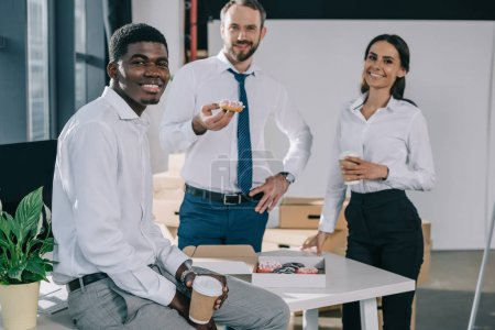 happy multiethnic coworkers holding paper cups with coffee to go and smiling at camera in new office