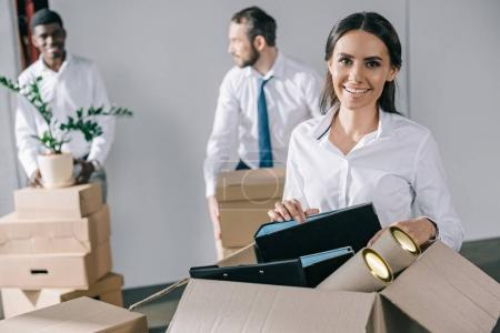 happy young businesswoman unpacking box with office supplies and smiling at camera while male colleagues standing behind in new office