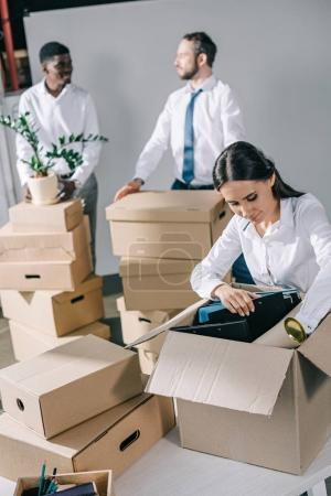 young businesswoman unpacking cardboard box and multiethnic men standing behind in new office