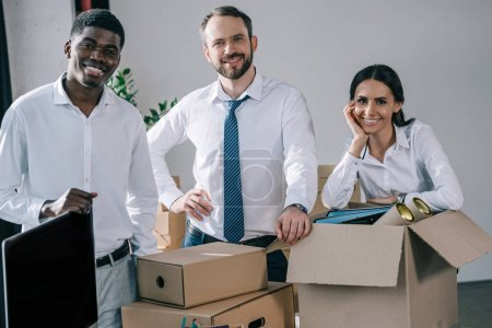 Photo for Happy multiethnic colleagues smiling at camera while unpacking cardboard boxes in new office - Royalty Free Image