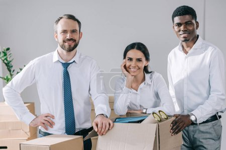 Photo for Happy multiracial colleagues smiling at camera and unpacking boxes in new office - Royalty Free Image