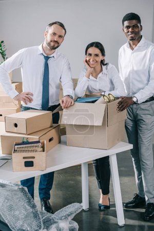 happy multiethnic coworkers smiling at camera and unpacking boxes in new office