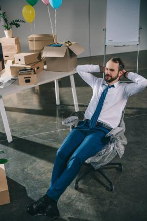 high angle view of businessman sitting with hands behind head in new office