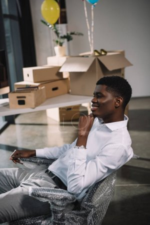 smiling young african american businessman sitting at workplace in new office