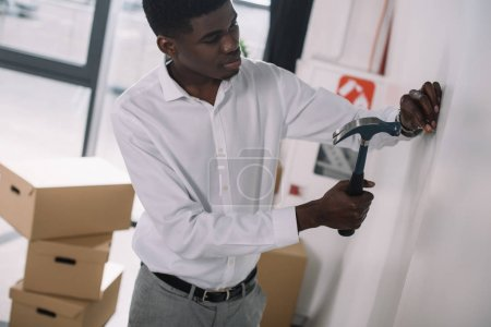 young african american businessman hammering nail in new office
