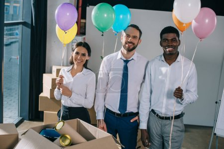 Photo for Happy multiracial colleagues holding colorful balloons and smiling at camera in new office - Royalty Free Image