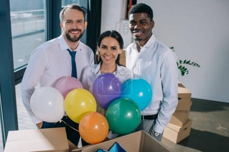 happy multiethnic coworkers holding colorful balloons and smiling at camera in new office
