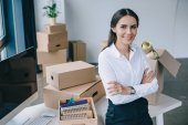 young businesswoman with crossed arms smiling at camera while sitting on table in new office