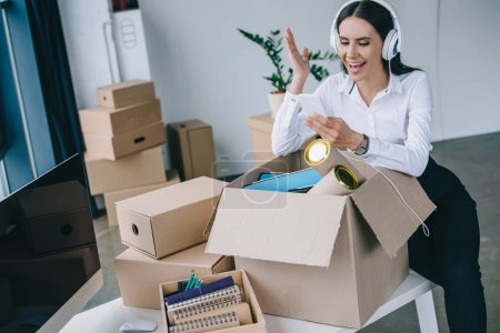 happy businesswoman in headphones using smartphone while unpacking boxes in new office