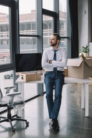 Photo for Businessman with crossed arms sitting on table and looking away in new office - Royalty Free Image