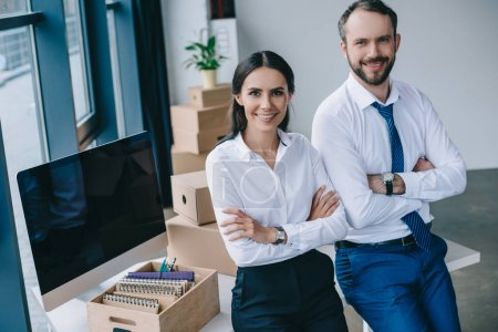 confident business people with crossed arms smiling at camera at new workplace