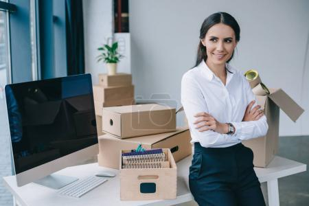 beautiful young businesswoman with crossed arms smiling and looking away in new office
